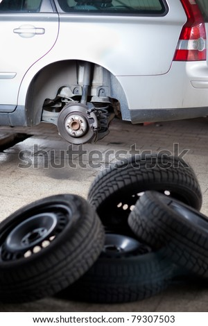 mechanic changing a wheel of a modern car (shallow DOF; color toned image) - stock photo