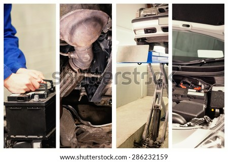 Mechanic changing car battery against mechanic under car in garage - stock photo