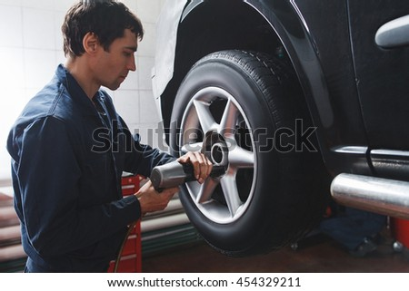 Mechanic changing car wheel in auto repair shop. Closeup of serviceman with tools working near castor of automobile in garage. - stock photo