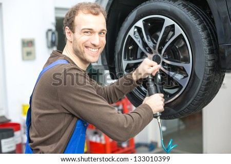 Mechanic changing the wheel on a car hydraulic lift - stock photo
