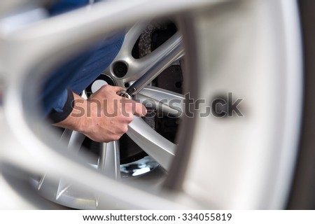 Mechanic changing tires at a tire service center, seen through the light weight alloy rim of a spare - stock photo