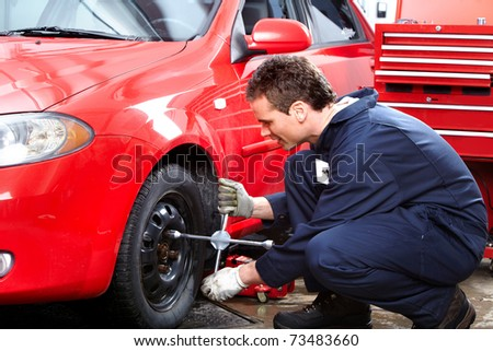 Mechanic changing wheel on car with a wrench.