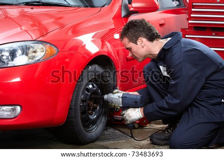 Mechanic changing wheel on car with impact wrench. - stock photo