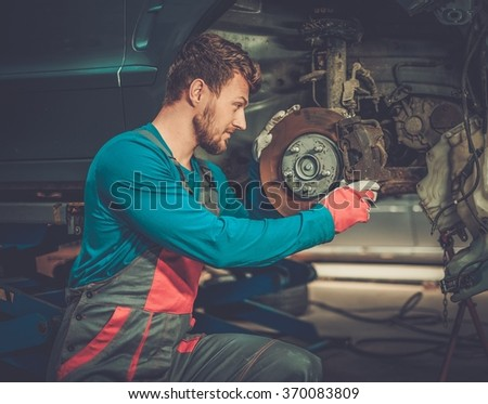 Mechanic checking car brake system in a workshop - stock photo