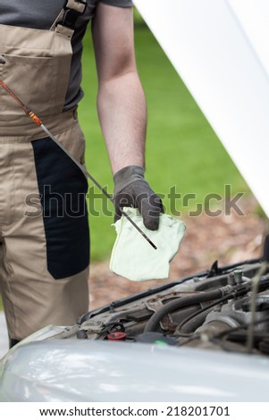 Mechanic checking oil level in a car - stock photo