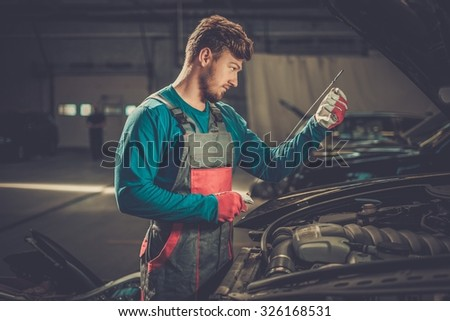 Mechanic checking oil level in a car workshop - stock photo