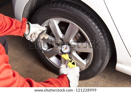 Mechanic checking the air pressure of a car wheel - stock photo