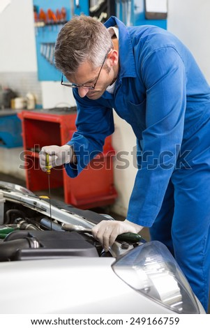 Mechanic checking the oil of car at the repair garage