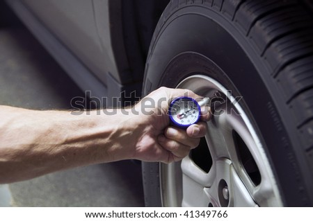 Mechanic checking tire pressure for increased gas mileage - stock photo