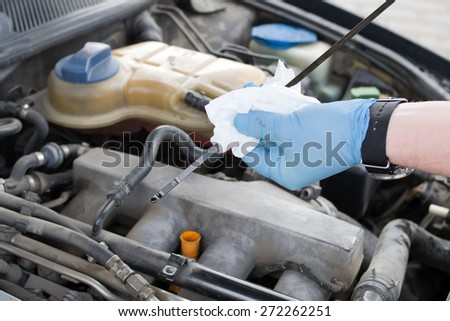 Mechanic checks the oil level in the engine - stock photo