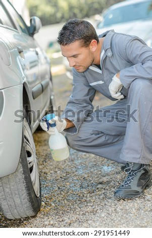 Mechanic cleaning a car - stock photo