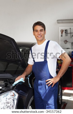 mechanic cleaning car engine and looking at camera. Copy space - stock photo