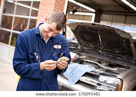 Mechanic: Counting money from repairs. - stock photo