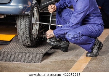 Mechanic Crouching While Fixing Car Tire - stock photo
