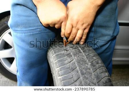 Mechanic deflating vehicle tyre  - stock photo