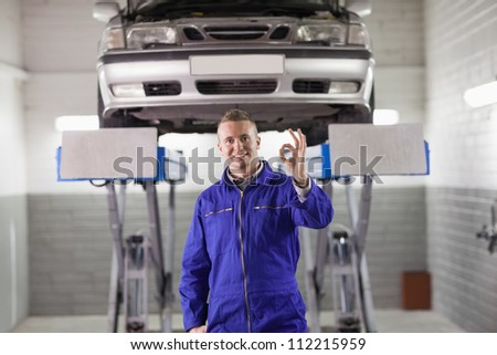 Mechanic doing a gesture with his hand in a garage - stock photo