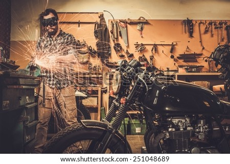 Mechanic doing lathe works in motorcycle customs garage  - stock photo