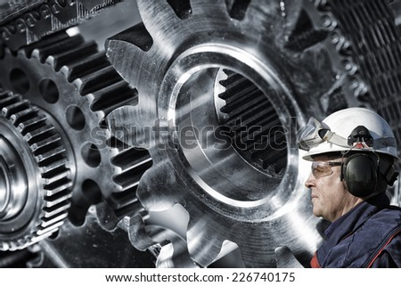 mechanic, engineer with large cogwheels machinery in background - stock photo