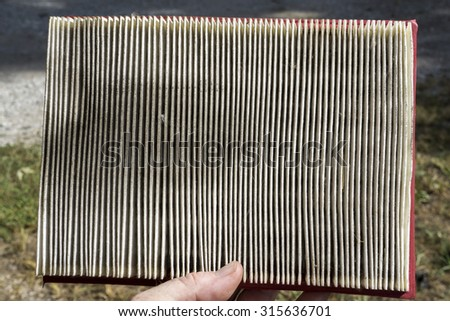 Mechanic examining a dirty air filter taken from a customer's car. - stock photo