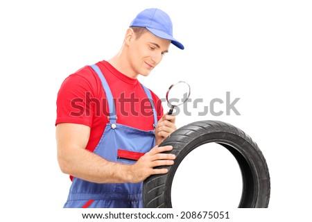 Mechanic examining tire through magnifying glass isolated on white background - stock photo