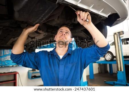 Mechanic examining under the car at the repair garage - stock photo