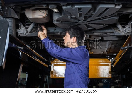 Mechanic Examining Underneath Lifted Car - stock photo