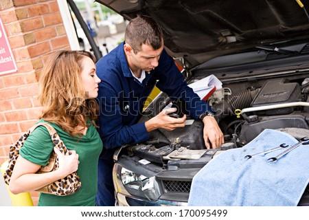 Mechanic: Explaining repair work to customer. - stock photo