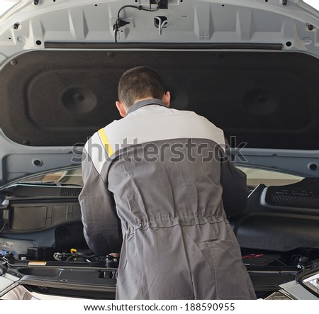 Mechanic fixes car in workshop. - stock photo