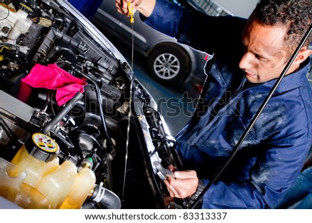 Mechanic fixing a car at the garage - stock photo