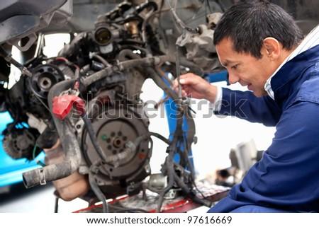 Mechanic fixing a car at the repair shop - stock photo