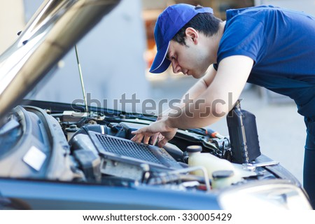 Mechanic fixing a car engine - stock photo