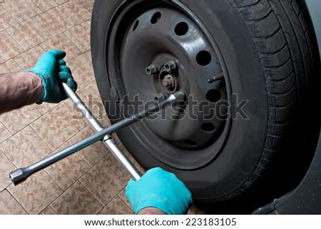 mechanic fixing a car wheel - stock photo