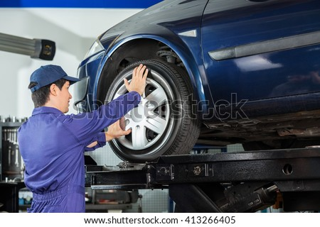 Mechanic Fixing Alloy To Car Tire - stock photo