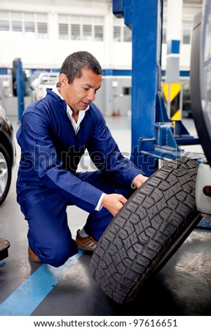 Mechanic fixing car wheel after a puncture - stock photo