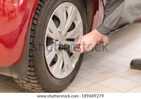Mechanic fixing car wheel at service. - stock photo