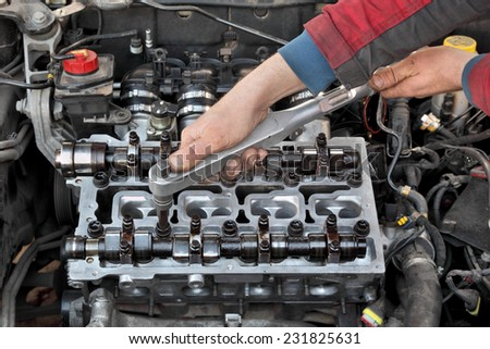 Mechanic fixing cylinder head with two camshaft of car engine with socket wrench - stock photo
