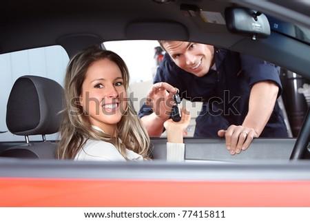Mechanic handing woman automobile keys. Auto repair - stock photo