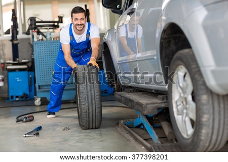 mechanic hands in blue uniform pushing a black tyre in a workshop - stock photo