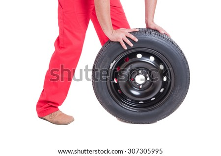 Mechanic hands pushing a new car wheel isolated on white