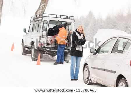 Mechanic helping woman with broken car snow assistance road winter - stock photo