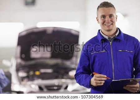 Mechanic holding a clipboard and a pen next to a car in a garage - stock photo