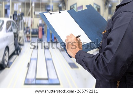 mechanic holding a clipboard of service order for maintaining car at the repair shop - stock photo