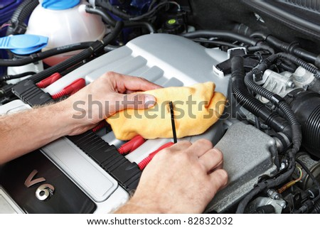 Mechanic holding a dip stick checking the engine oil on a v6 sports car - stock photo