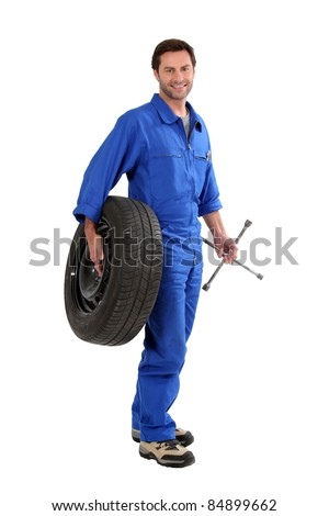 mechanic holding a tire - stock photo