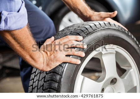 Mechanic Holding Car Tire At Garage - stock photo