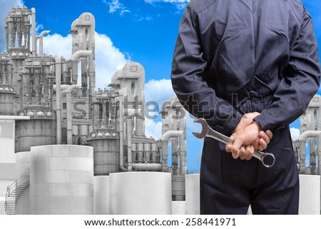 mechanic holding tools for maintaining at petrochemical Industrial plant with blue sky - stock photo