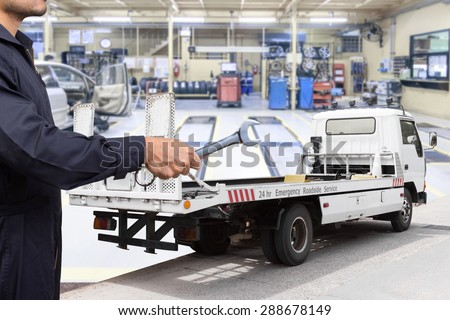 Mechanic holding wrench with towing truck prepared for rescue at auto repair shop - stock photo