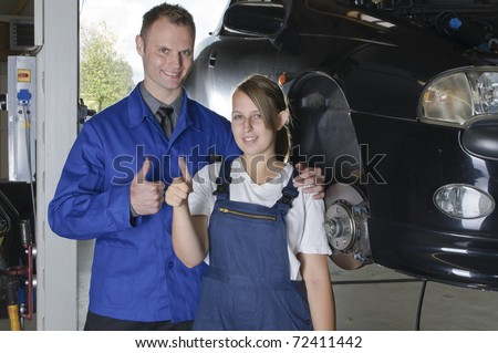 Mechanic in blue overalls in front of a car with the hood open smiles, pleased at the camera and makes the 'thumbs up' gesture - stock photo