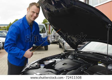"""Mechanic in blue overalls in front of a car with the hood open, """"thumbs up"""" - stock photo"""