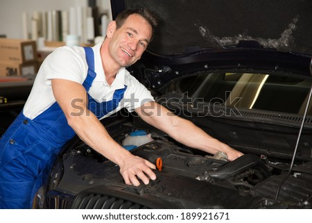 Mechanic in garage or workshop repairing car